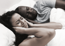 man sleeping and woman covering her ears